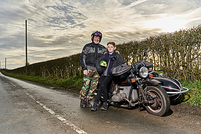 Portrait of senior male motorcyclist and grandson sitting on motorcycle at roadside - p429m1227037 by GS Visuals