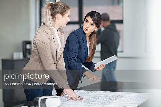 Two young women with tablet and VR glasses working on blueprint in office - p300m1550264 by zerocreatives