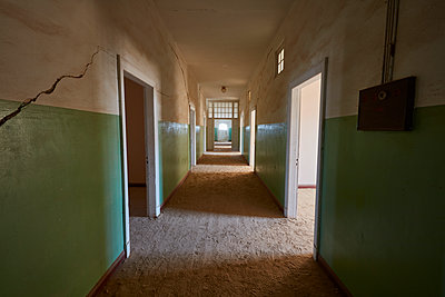 A view of a corridor in a derelict building full of sand. Vivid green coloured walls. Shadows - p1100m1489981 by Mint Images