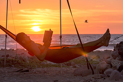 Side view of man reading book while lying in hammock at beach during sunset - p1166m1210822 by Cavan Images
