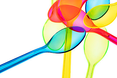 Coloured transparent plastic disposable spoons on white background - p1302m2045580 by Richard Nixon