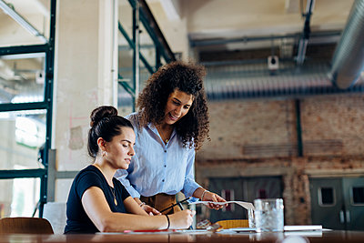 Two young businesswomen talking at conference table in loft office - p300m2144441 by Sofie Delauw