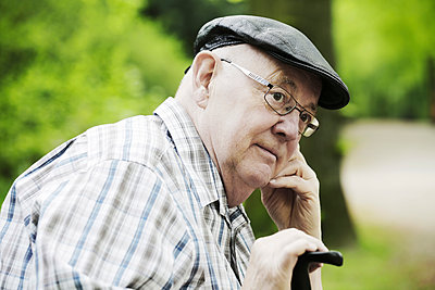 Germany, rth Rhine Westphalia, Cologne, Senior man with cap and glasses in park, close up - p300m2207273 by Jan Tepass