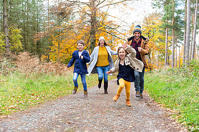 Happy family playing while running together on forest path - p300m2257432 by William Perugini