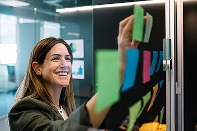 Excited businesswoman brainstorming using sticky notes on glass wall at office - p300m2277749 by Xavier Lorenzo