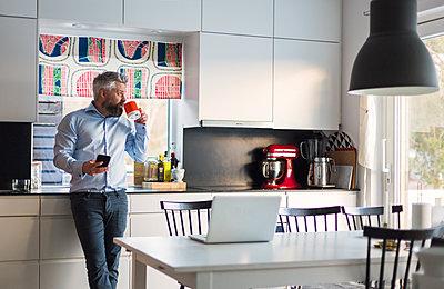 Man drinking coffee in kitchen - p352m1536606 by Calle Artmark