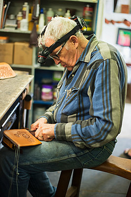 A mature man working on a leather piece; Waimea, Island of Hawaii, Hawaii, United States of America - p442m1147865 by Judi Angel