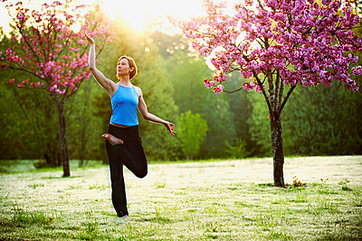 Woman in yoga pose in park - p924m674343f by Pete Saloutos