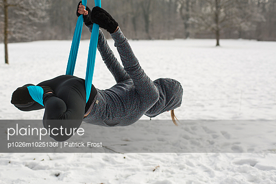 Young woman practicing aerial yoga outdoors - p1026m1025130f by Patrick Frost