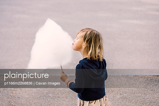 Cute young girl 3-4 years old eating cotton candy - p1166m2268836 by Cavan Images