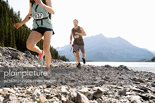 Runners in marathon bibs running along craggy, sunny lakeside - p1192m2129224 by Hero Images
