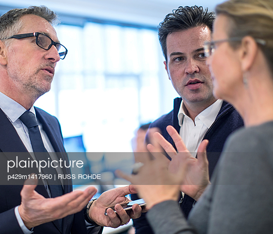 Colleagues in office having discussion - p429m1417960 by RUSS ROHDE