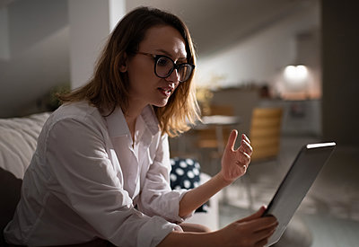 Professional businesswoman with tablet working at home - p1166m2234304 by Cavan Images