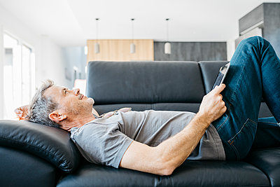 Smiling mature man with digital tablet day dreaming while lying down on sofa in living room - p300m2266584 by Josep Rovirosa