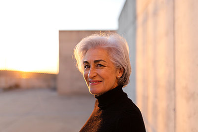 Mature woman with gray hair smiling in front of wall - p300m2281472 by PICUA ESTUDIO