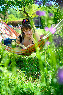 Young woman reading book in a hammock - p427m2203604 by Ralf Mohr