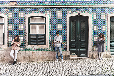 Three young adults standing in street, looking at their own smartphones, Lisbon, Portugal - p429m1408042 by William Perugini