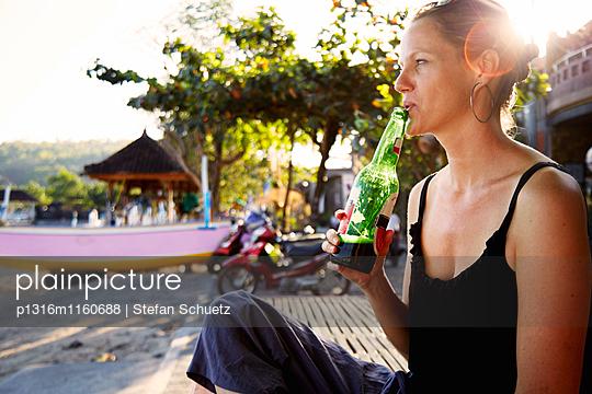 Frau trinkt ein Bier am Strand, Padang Bai, Bali, Indonesien - p1316m1160688 von Stefan Schuetz