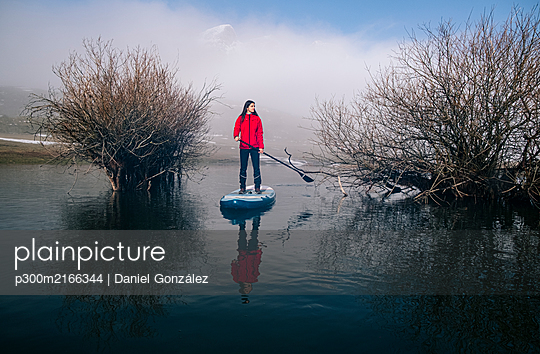 Woman stand up paddle surfing on a lake - p300m2166344 by Daniel González