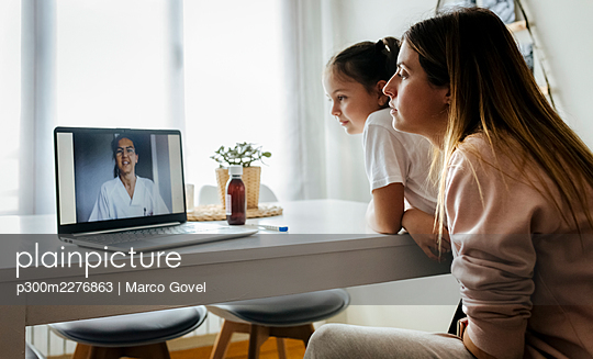 Girl and woman listening to female pediatrician on video call through laptop at home - p300m2276863 by Marco Govel