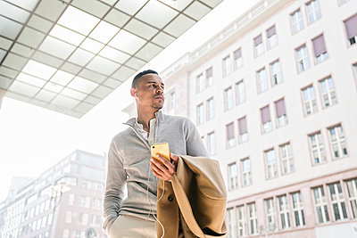Portrait of businessman using earphones and smartphone in the city - p300m2143393 von Hernandez and Sorokina