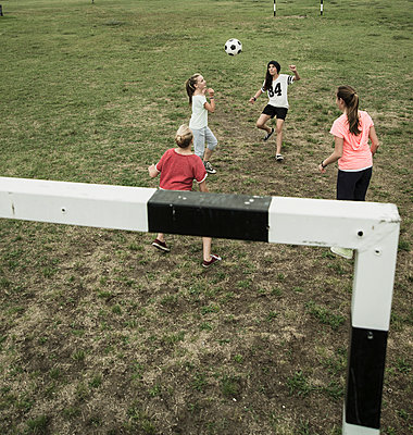 Four female teenage friends playing soccer, elevated view - p300m950161f by Uwe Umstätter