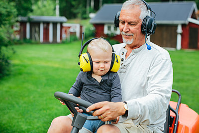 Grandfather with grandson on ride-on lawn mower - p312m1121701f by Anna Rostrom