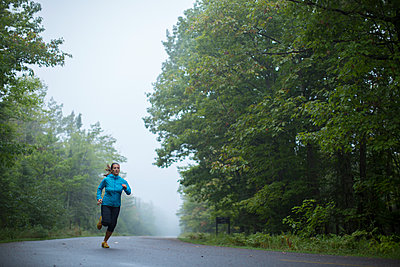 An adult woman running down a remote road on a foggy morning - p343m1168491 by Woods Wheatcroft