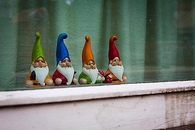 4 Gartenzwerge in einem Fenster - p627m1035392 von Christian Reister