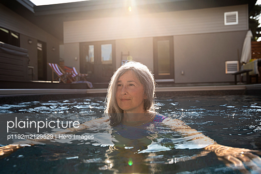 Serene senior woman swimming in sunny, summer swimming pool - p1192m2129529 by Hero Images