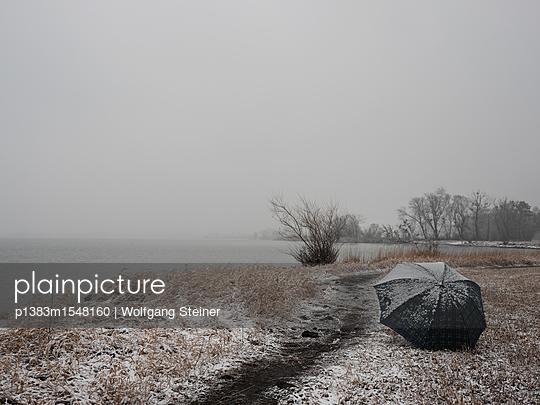 Angeschneiter Regenschirm am Seeufer - p1383m1548160 von Wolfgang Steiner