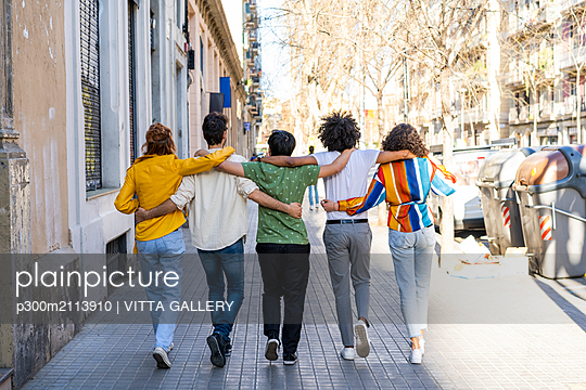 Rear view of group of friends walking arm in arm in the city - p300m2113910 von VITTA GALLERY