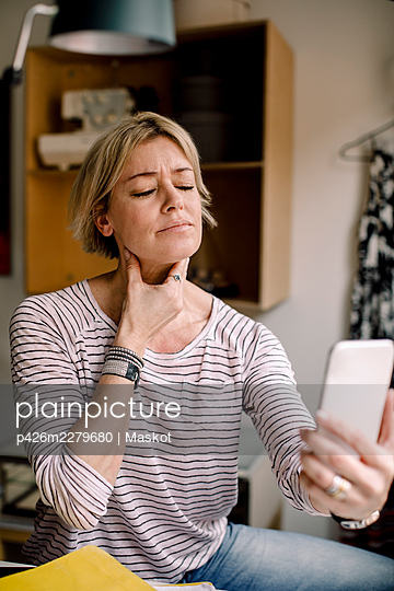 Blond woman consulting with doctor through smart phone at home - p426m2279680 by Maskot
