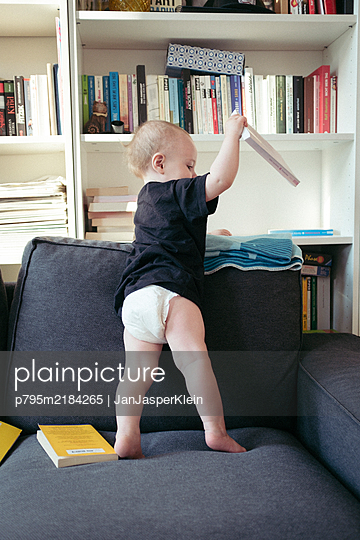 Baby boy clears out book shelf - p795m2184265 by JanJasperKlein