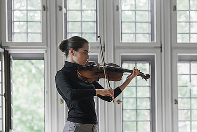 Side view of confident woman playing violin while standing against windows in mansion - p1166m2011270 by Cavan Images
