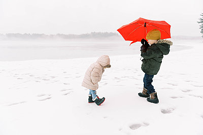 A brother and sister having fun in the wintery rain. - p1166m2157461 by Cavan Images