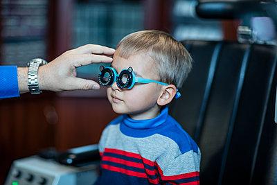 Boy doing eye test at optometrist - p300m1189376 by zerocreatives