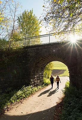 Mother and daughter walking underneath railway bridge, Mehren, Rheinland-Pfalz, Germany - p429m1514015 by Mischa Keijser