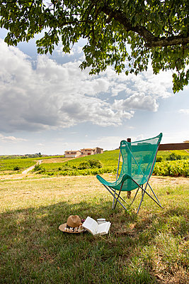 Empty camping chair with book and hat in the grass. - p948m2142122 by Sibylle Pietrek
