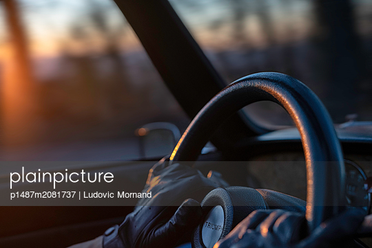 Hand on the wheel at sunset - p1487m2081737 by Ludovic Mornand