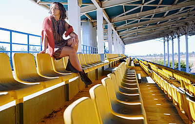 Thoughtful woman sitting in empty stadium - p1166m2107053 by Cavan Images
