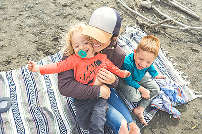 Happy mother with two sons sitting on blanket during picnic - p1166m2202003 by Christopher Kimmel / Alpine Edge Photography