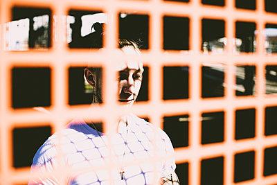 Mann steht hinter einem vergitterten Fenster - p1267m2263394 von Jörg Meier