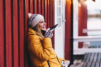 Happy tourist using smartphone at Hamnoy, Lofoten, Norway - p300m2166479 by Daniel González