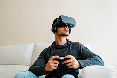 Young man playing video game through virtual reality simulator - p300m2251134 by Ezequiel Giménez