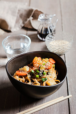 Bowl of vegan pasta with vegetables and sesame seeds - p300m2251356 by Eva Gruendemann