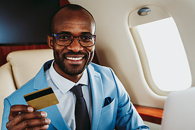 Smiling male entrepreneur with credit card in airplane - p300m2257042 by OneInchPunch