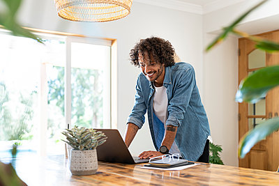 Smiling businessman working on laptop at home - p300m2276548 by Steve Brookland