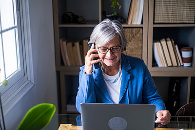 Smiling senior female professional talking on mobile phone while looking at laptop in home office - p300m2276601 by Simona Pilolla