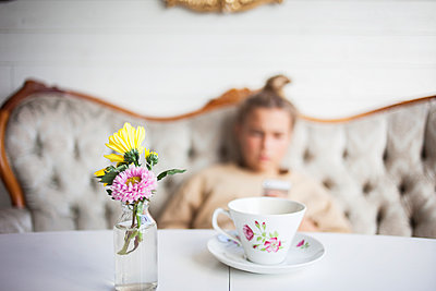 Cup and flowers on table, girl on background - p312m1471876 by Christina Strehlow